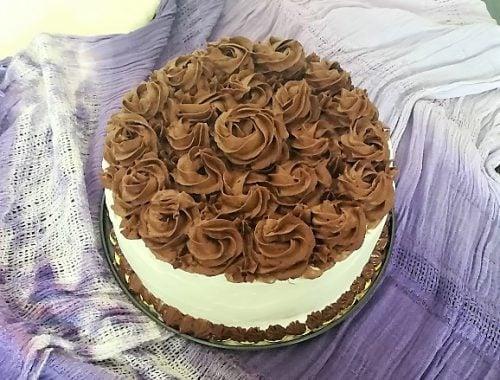 biały tort z czekoladowymi kwiatami na fioletowym tle